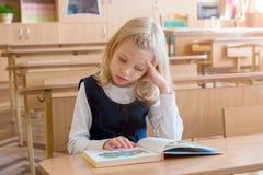 La ragazza nel primo grado, sta sedendosi allo scrittorio con il libro Fotografia Stock Libera da Diritti