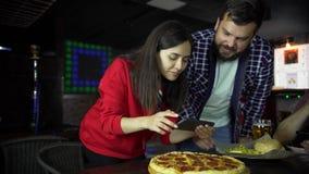 La ragazza nel pub prende le immagini di pizza sul vostro smartphone stock footage