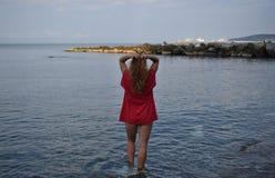 La ragazza nel rosso sta sulla spiaggia e tocca i suoi capelli immagini stock