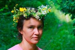 La ragazza nel sopporto per anima dei fiori nel legno Immagini Stock
