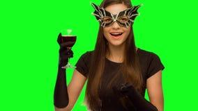 La ragazza nel teatro della maschera e un vestito nero, in sigillo beve il vino, buon anno ed invia un bacio dell'aria stock footage