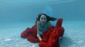 La ragazza nel vestito gioca con un underwater rosso del panno al fondo dello stagno ed esamina la macchina fotografica stock footage