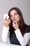 La ragazza nell'affare copre il rossetto che guarda di piccolo specchio Fotografia Stock