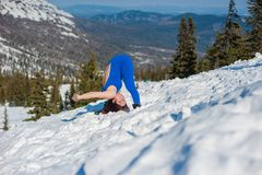 La ragazza nell'attrezzatura blu che fa yoga sopra una montagna dentro Fotografie Stock Libere da Diritti