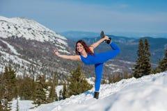 La ragazza nell'attrezzatura blu che fa yoga sopra una montagna in w Immagini Stock Libere da Diritti
