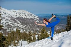 La ragazza nell'attrezzatura blu che fa yoga sopra una montagna in w Fotografia Stock