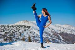 La ragazza nell'attrezzatura blu che fa yoga sopra una montagna in w Fotografia Stock Libera da Diritti