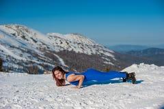La ragazza nell'attrezzatura blu che fa yoga sopra una montagna in w Fotografie Stock Libere da Diritti