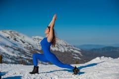 La ragazza nell'attrezzatura blu che fa yoga sopra una montagna in w Immagini Stock