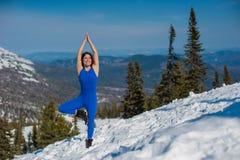 La ragazza nell'attrezzatura blu che fa yoga sopra una montagna in w Immagine Stock