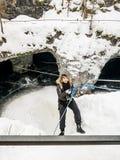 La ragazza nell'ingranaggio di alpinismo che scende su una corda al Immagine Stock