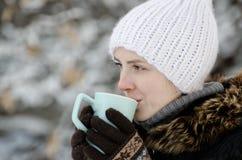 La ragazza nell'inverno copre il tè bevente da una tazza, vista laterale, primo piano Fotografia Stock Libera da Diritti