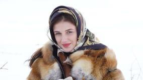 La ragazza nell'inverno copre sorridere e lo sguardo alla macchina fotografica 4K video d archivio