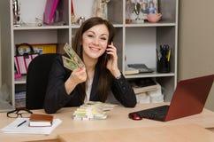 La ragazza nell'ufficio con un pacco delle banconote che parla sul telefono Immagini Stock Libere da Diritti