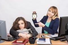 La ragazza nell'ufficio con un sorriso, indicare le ore ed il collega torturato Immagini Stock Libere da Diritti