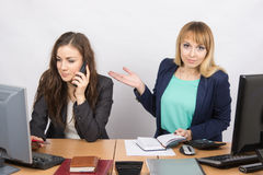 La ragazza nell'ufficio imbarazzata indica il collega che parla sul telefono Fotografia Stock