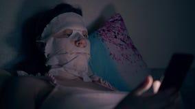 La ragazza nella cima rosa con la maschera bianca dello skincare si trova sul cuscino stock footage