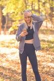 La ragazza nella foresta legge il messaggio ed aderisce alla sua testa fotografia stock libera da diritti