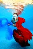 La ragazza nella maschera bianca nuota underwater con i tessuti rossi e blu sui precedenti del tramonto e di esame della macchina Immagini Stock