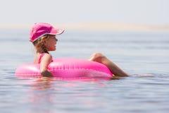La ragazza nella nuotata del cappuccio nel fiume si è seduta sul cerchio di nuoto Immagini Stock