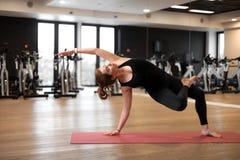 La ragazza nella palestra fa l'yoga per tenersi nella forma o nel peso in eccesso di controllo fotografia stock libera da diritti