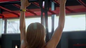 La ragazza nella palestra stringe sulla barra trasversale archivi video