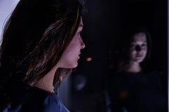 La ragazza nella riflessione nella finestra Fotografia Stock
