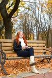La ragazza nella stagione di autunno ascolta musica sull'audio giocatore con le cuffie, si siede sul banco in parco della città,  Fotografia Stock