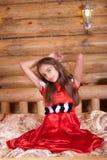 La ragazza nello Spagnolo rosso veste la seduta sulla base Fotografia Stock Libera da Diritti