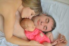 La ragazza neonata è caduto addormentato con la suoi madre e padre Immagine Stock