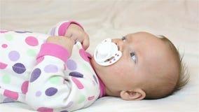 La ragazza neonata che si trova sullo strato e succhia la tettarella stock footage