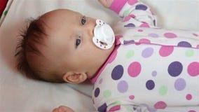 La ragazza neonata che si trova sullo strato e succhia la tettarella archivi video