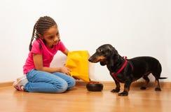 La ragazza nera alimenta il suo animale domestico del cane con alimento Fotografia Stock