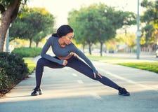La ragazza nera sportiva nell'allenamento copre l'allungamento su un percorso i della bici Fotografie Stock Libere da Diritti