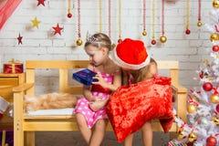La ragazza non ha gradito il regalo che gli desse un'altra ragazza vestita come Santa Claus Fotografia Stock