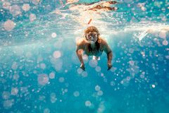 La ragazza nuota con una maschera underwater nel mare immagine stock libera da diritti