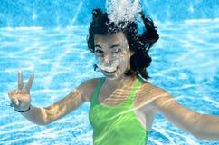 La ragazza nuota nella piscina subacquea, adolescente attivo felice si tuffa e si diverte sotto l'acqua, forma fisica del bambino fotografia stock libera da diritti