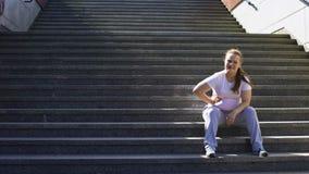 La ragazza obesa ritiene i dolori laterali dopo gli allenamenti gravosi all'aperto, dolore in fegato stock footage