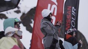 La ragazza in occhiali da sole applaude dentro campeggia tra altra gente Stazione sciistica Bandierina d'ondeggiamento video d archivio