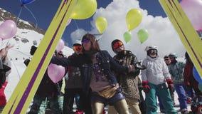 La ragazza in occhiali da sole cede gli aerostati alla gente sulla stazione sciistica intrattenimento stock footage