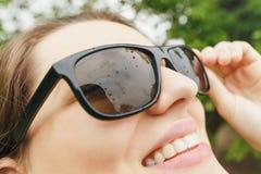 La ragazza in occhiali da sole piove esaminando il cielo Immagini Stock