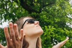 La ragazza in occhiali da sole piove esaminando il cielo Fotografie Stock