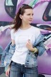 La ragazza in occhiali da sole si avvicina ai graffiti Fotografia Stock