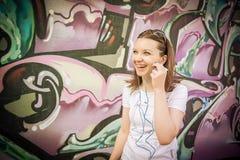 La ragazza in occhiali da sole si avvicina ai graffiti Fotografie Stock Libere da Diritti