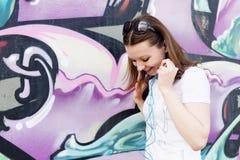 La ragazza in occhiali da sole si avvicina ai graffiti Immagini Stock