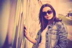 La ragazza in occhiali da sole si avvicina ai graffiti Fotografie Stock