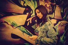 La ragazza in occhiali da sole si avvicina ai graffiti Fotografia Stock Libera da Diritti