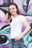 La ragazza in occhiali da sole si avvicina alla parete dei graffiti Fotografie Stock