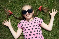 La ragazza in occhiali da sole si trova su erba verde, vestita in vestiti rosa con i cuori, sole luminoso, l'estate all'aperto, v immagine stock libera da diritti