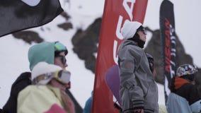 La ragazza in occhiali da sole sta dentro campeggia tra altra gente Stazione sciistica Bandiere d'ondeggiamento video d archivio